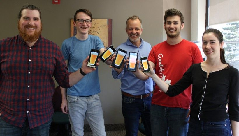 Grady Williams (left) and Isaac Lohnes (second from left) display an app they created as part of their co-op program, along with their co-workers. Both Isaac and Grady are now on immediaC's management team.